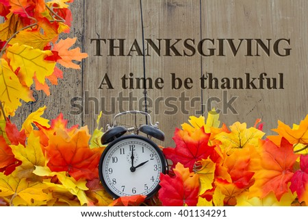 A time to be Thankful, Autumn Leaves and Alarm Clock with grunge wood with text Thanksgiving a time be thankful - stock photo