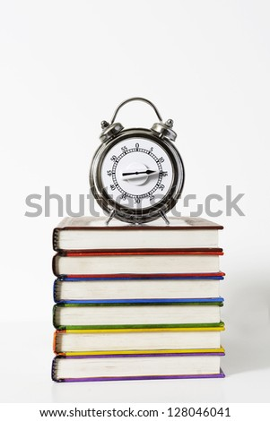 A timer sitting on colorful hard bound books - stock photo