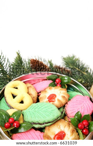 A tin of colorful Christmas cookies surrounded by pine branches.  White background with room for text.