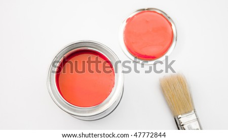 A tin of red paint with a brush and a lid - stock photo