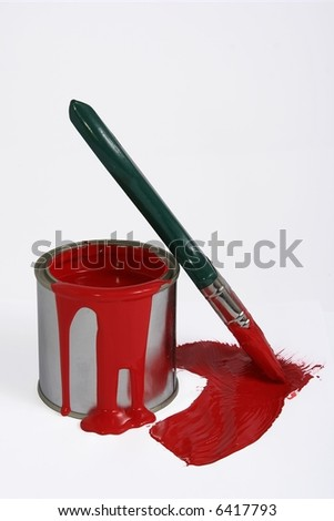A tin of red paint with paint spilling down the side and a green paint brush - stock photo