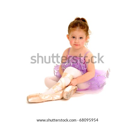 A tiny ballerina tries on pointe shoes.