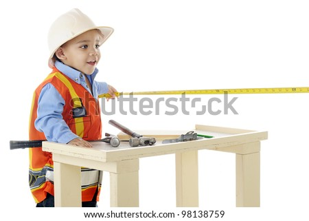 "A tiny biracial ""construction worker"" using a tape measure by his workbench.  On a white background."