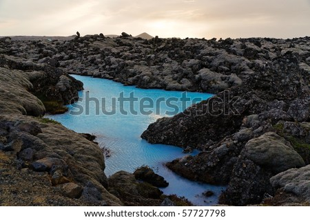 A tiny blue lake surrounded by black lava at the Blue Lagoon region near Reykjavik - stock photo
