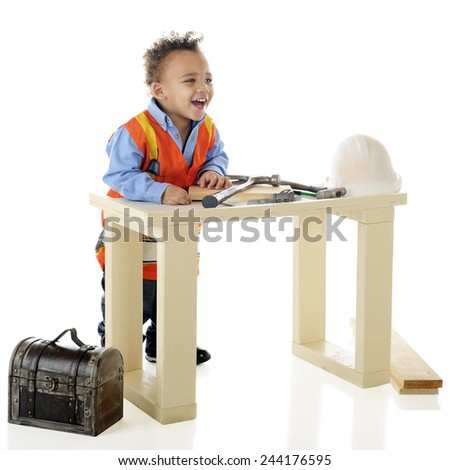 A tiny construction working laughing behind his tool-covered work bench.  On a white background.