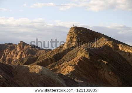 A tiny figure on a mountaintop in Death Valley National Park. - stock photo