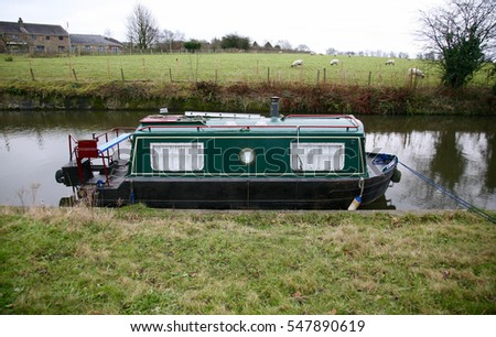 A tiny narrow boat on the Leeds Liverpool Canal close to Wigan town centre, Lancashire, England