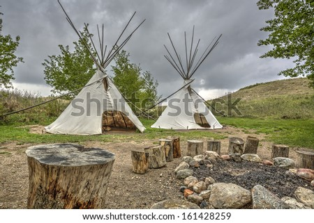 A tipi (also tepee and teepee) is a conical tent, traditionally made of animal skins, and wooden poles - stock photo