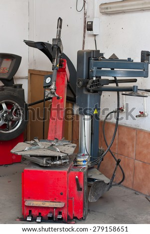 A tire changer device in an automobile repair shop, with a wheel balancing machine in the background.