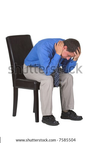 A tired and exhausted business man sitting on a chair with his head in his hands.  The image is isolated on a white background