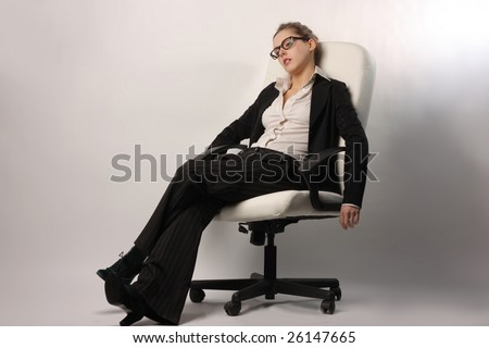 a tired beautiful businesswoman relaxing on a manager chair - stock photo