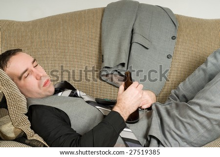 A tired businessman lying on a sofa and having a beer - stock photo