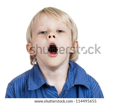 A tired cute young boy yawning. Isolated on white. - stock photo