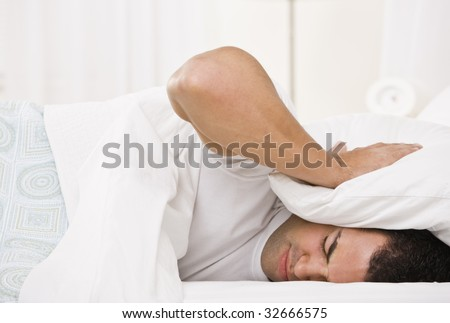 A tired looking man holding a pillow over his head and lying in bed.  Horizontally framed shot. - stock photo