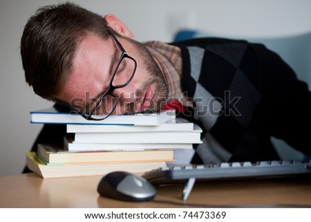 A tired nerdy man sleeping on a bunch of books in his office