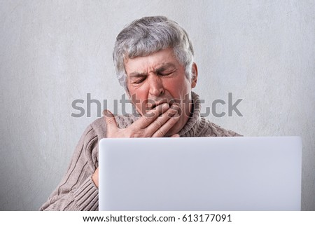 A tired old man yawning in frot of his laptop being fatigued while after writing his book. A mature man with gray hair holding his hand on his mouth. A hard work of senior man.