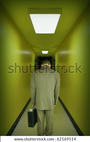 A tired, overworked, stressed business man is walking down a green tint hallway with his head down. Use it for a powerlessness, employment or worry concept.
