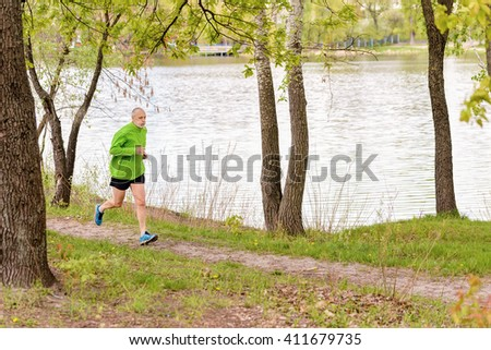 A tired senior man dressed in black and green is running in the park, close to the lake, during a gray spring day - stock photo