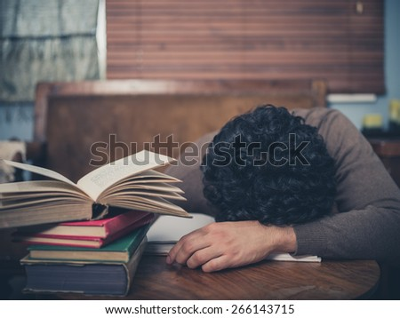 A tired student is asleep with his head on a coffee table surrounded by books - stock photo