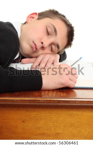 A tired, weary or bored student at desk sleeping or resting. - stock photo