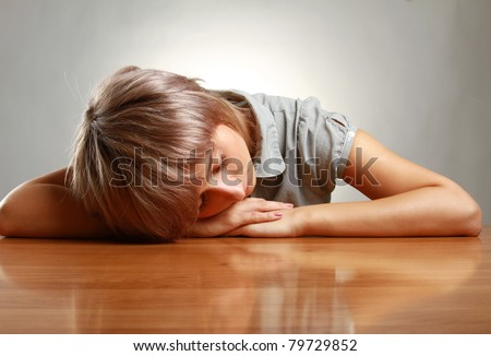 A tired woman sleeping on the desk, isolated on grey
