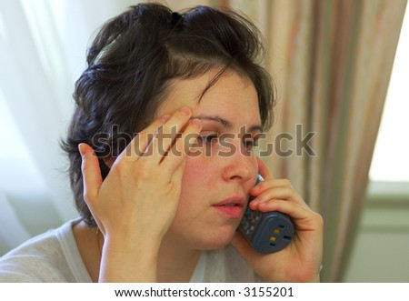 A tired young woman receives bad news on the phone... - stock photo