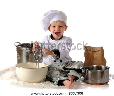 A toddler boy spinning a hand-held egg beater in a big bowl.  He's surrounded by pots and spilled flour.  Isolated on white. - stock photo