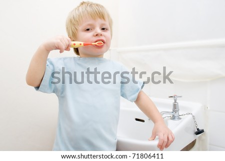 A toddler brushing his teeth in the bathroom at bedtime. - stock photo