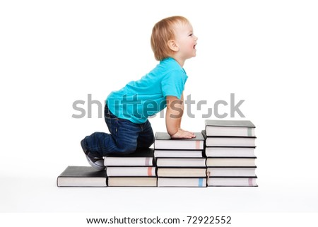 A toddler creeping for knowledge on the steps made of books - stock photo