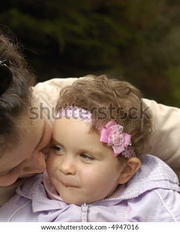 A toddler daughter listens mischievously to her mother on a bench in a park - stock photo