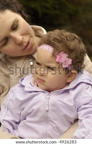 A toddler daughter listens to her mother on a bench in the park. - stock photo