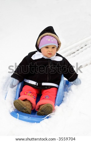 A toddler girl bewildered by her first ride in a snow on a sleigh/sledge. - stock photo