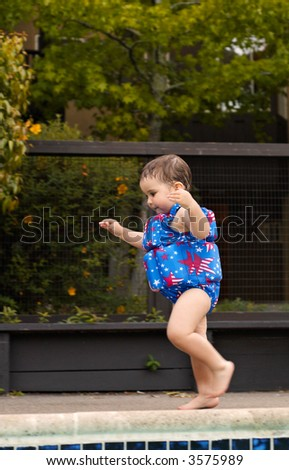 A toddler girl is running in the bulky colorful swimsuit .  Feet and hands are motion-blurred. - stock photo