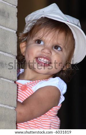 A toddler girl with a dimple on one cheek playing peek-a-boo