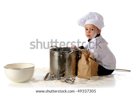 A toddler in a chef's outfit surrounded by cooking utensils and spilled flour. - stock photo