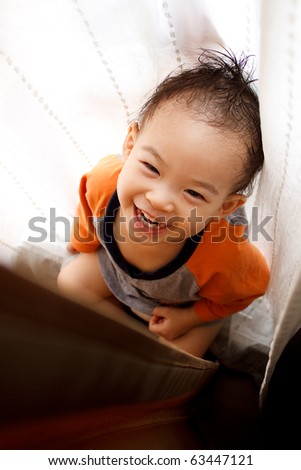 A toddler playing hide-and-seek in the middle of curtains - stock photo