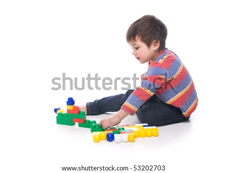 A toddler playing with a multicolored bricks - stock photo