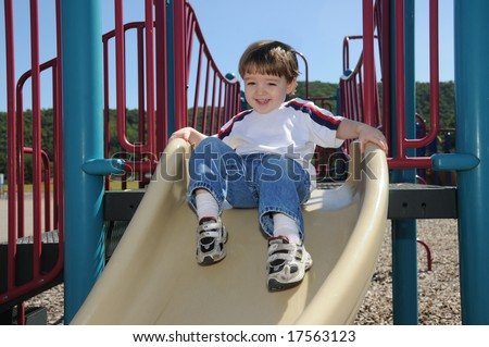 A toddler shows his excitement as he is about to take off on a slide in a neighborhood playground - stock photo