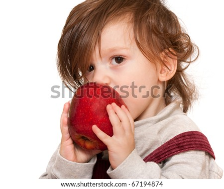 A toddler with long hair is eating a big red apple; isolated on the white background