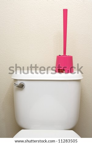 A toilet brush sitting on the back of a toilet - stock photo