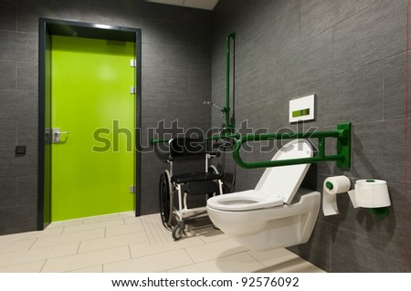 a toilet for disabled people with green bars, wheelchair and door - stock photo