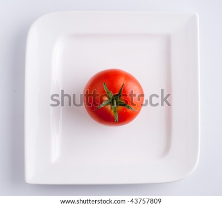 A tomato on a white plate - top view - stock photo