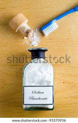 A toothbrush and a  bottle of Sodium Bicarbonate (baking soda) laid flat and shot from overhead on a wooden table.  Cork open and powder spilling on to table. - stock photo