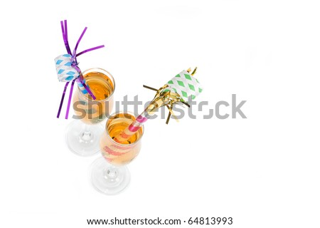 A top angled view of two New Year's Eve noisemakers in two glasses of champagne. - stock photo