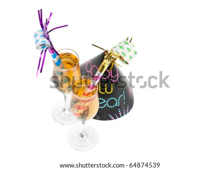 A top angled view of two New Year's Eve noisemakers in two glasses of champagne with a party hat on a white background. - stock photo