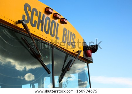 A top  front of a schoolbus over a blue sky - stock photo