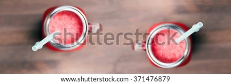 A top shallow dof view of a watermelon smoothies in a mason jars with tubes on wooden background. Selective focus on tubes - stock photo