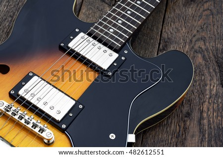 A top view image of a yellow and black electric guitar on a wooden table top.