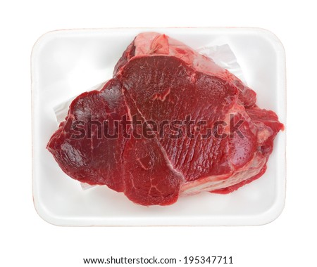 A top view of a boneless beef chuck roast in white tray.  - stock photo