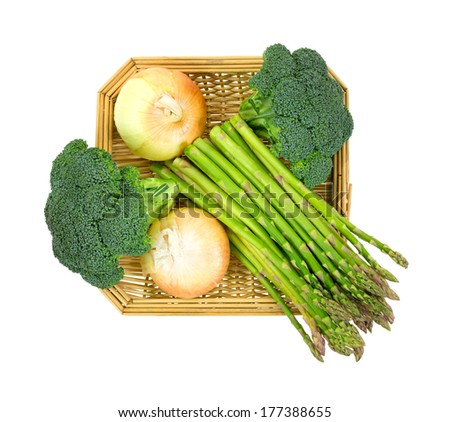 A top view of a combination of broccoli florets, asparagus, onion and celery in a basket on white background. - stock photo
